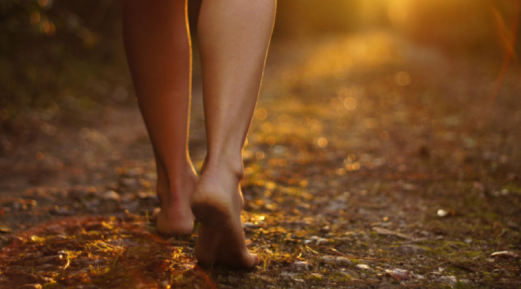 woman walking barefoot through a forest
