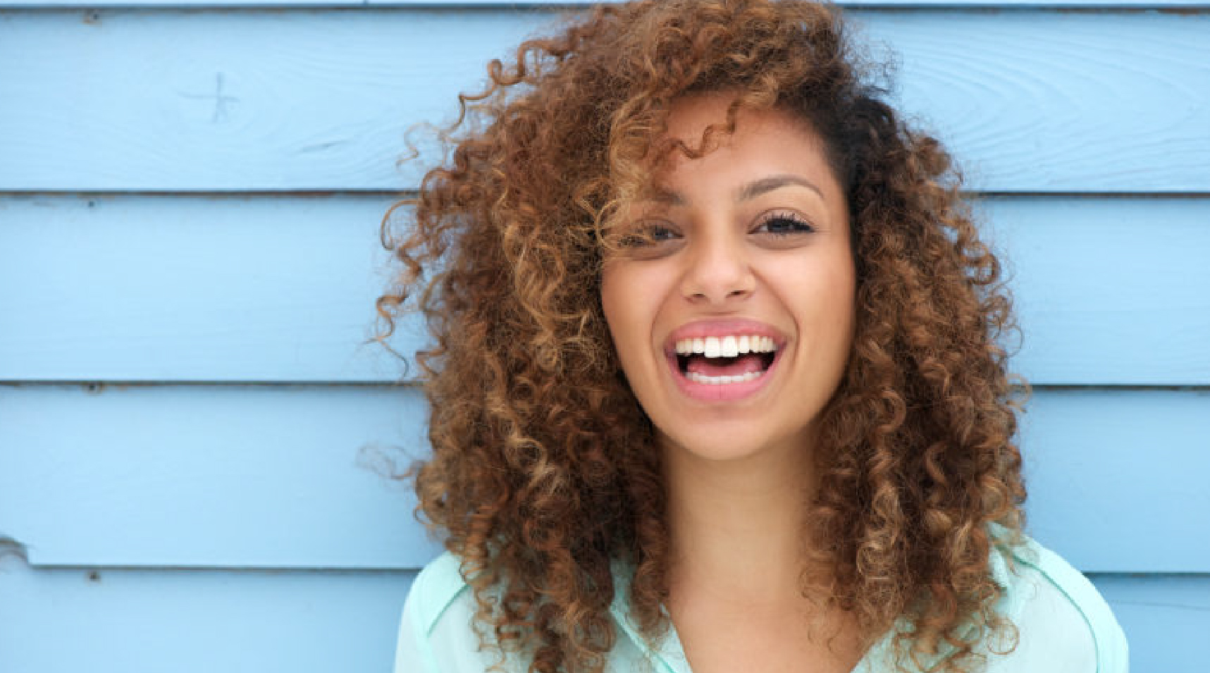Woman smiling wide while standing in front of a blue wall