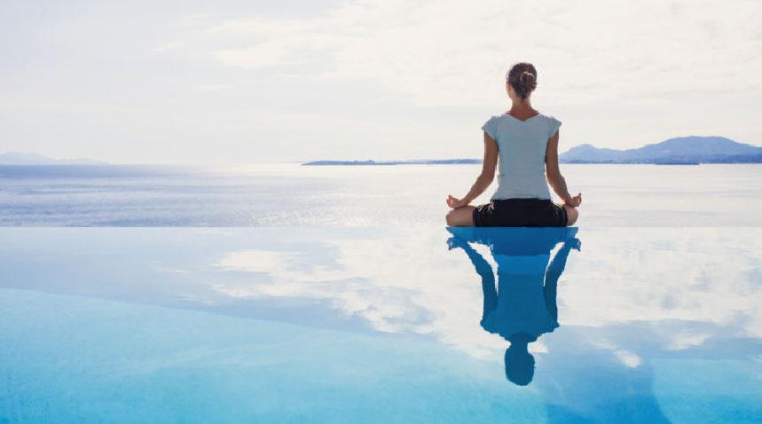 woman doing yoga as she faces the ocean