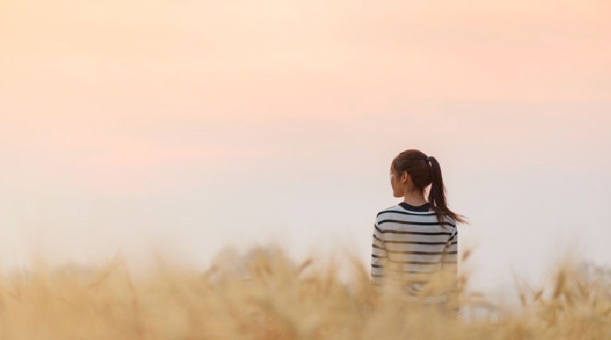 Asian woman standing in a field looking into the distant