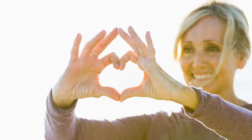 women smiling and holding her hands in the shape of a heart