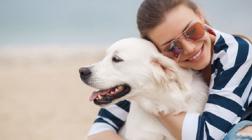 woman smiling and hugging a dog