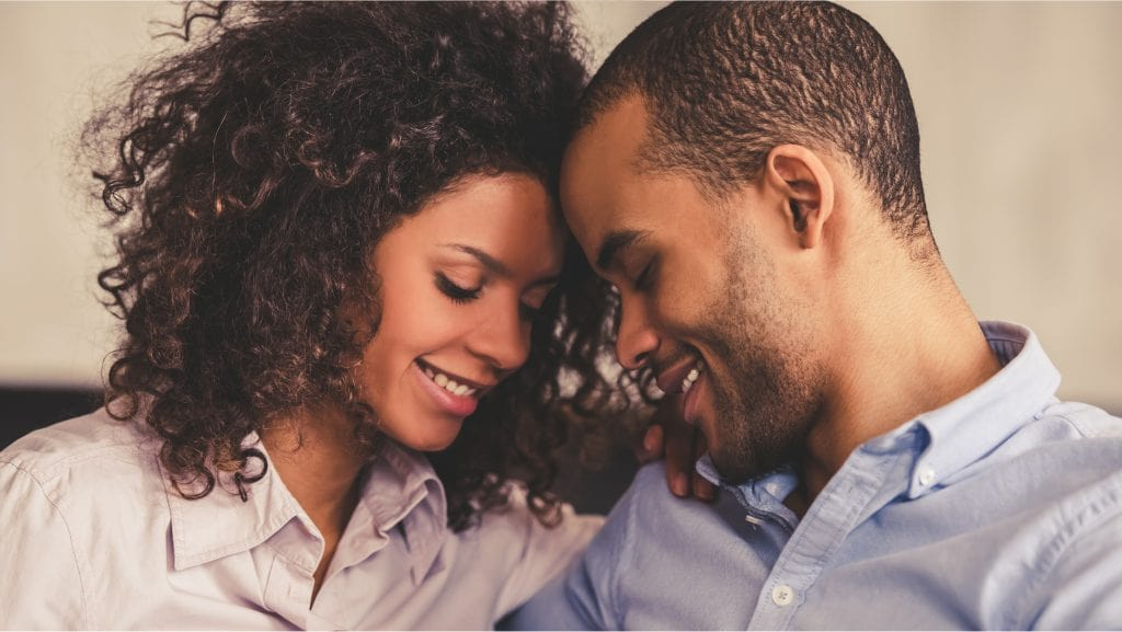 A couple having their foreheads against each other and smiling