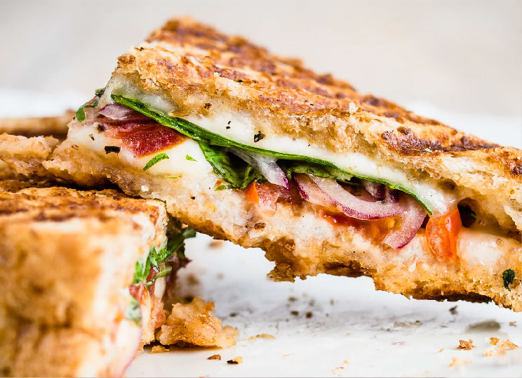 A sandwich with spinach, tomato, and onion
