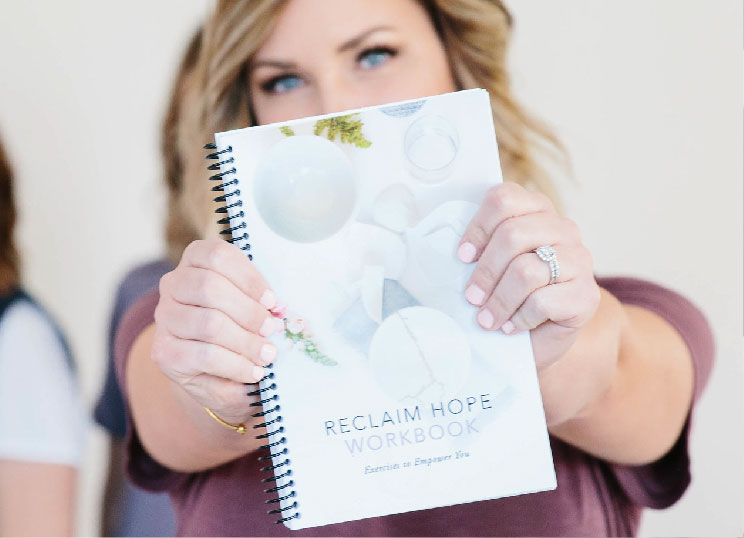 A woman holding the reclaim hope workbook in her hands
