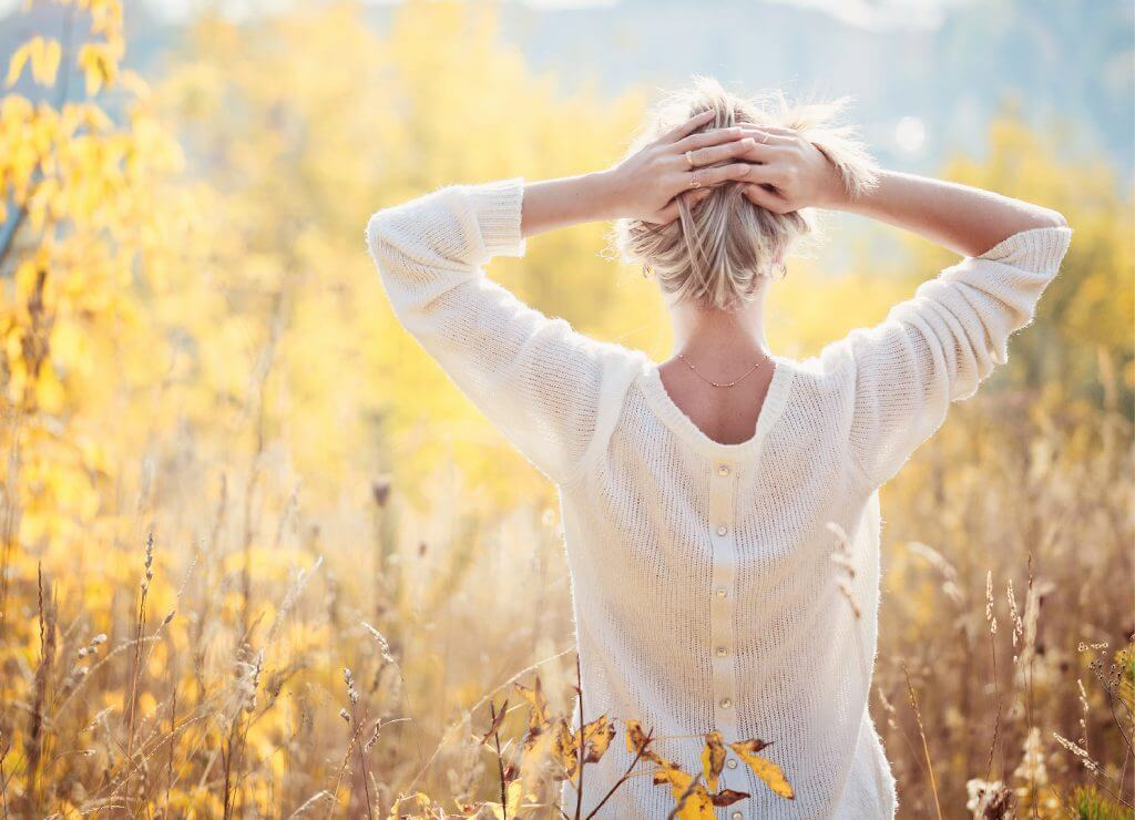 A woman standing in ther field of yellow plants and holding her hands over her head
