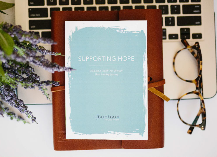 "A card with ""Supporting Hope"", a notebook and a pair of glasses on the laptop"