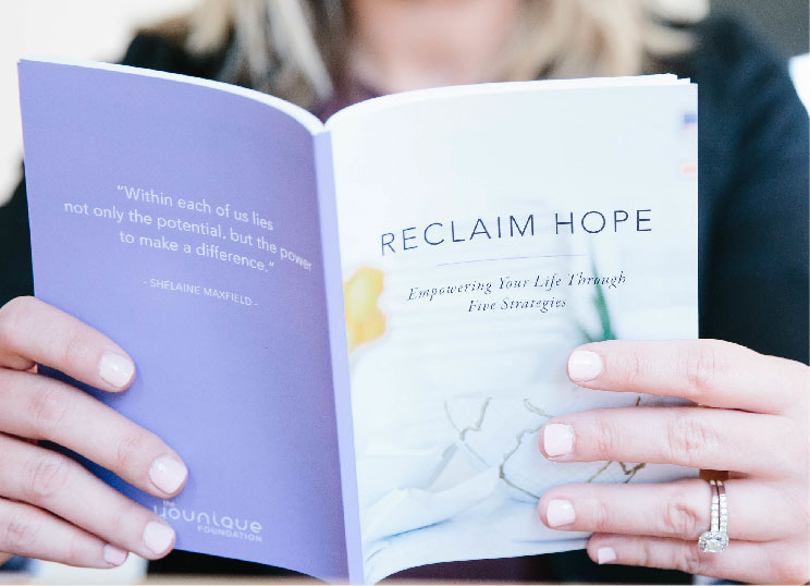 A woman reading a handbook about reclaim hope