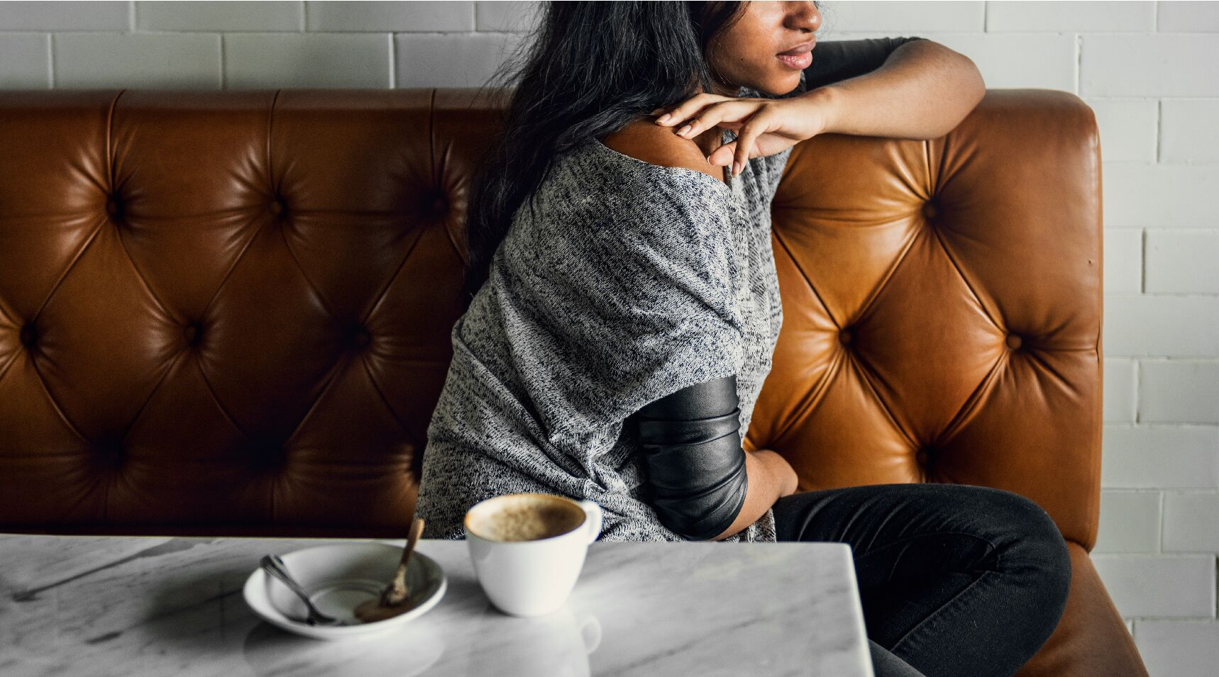 woman in a coffe shop sitting alone with a defensive posture