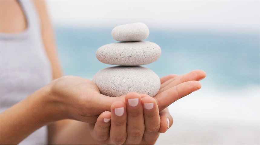 woman balancing three stones on top of each other in her hand