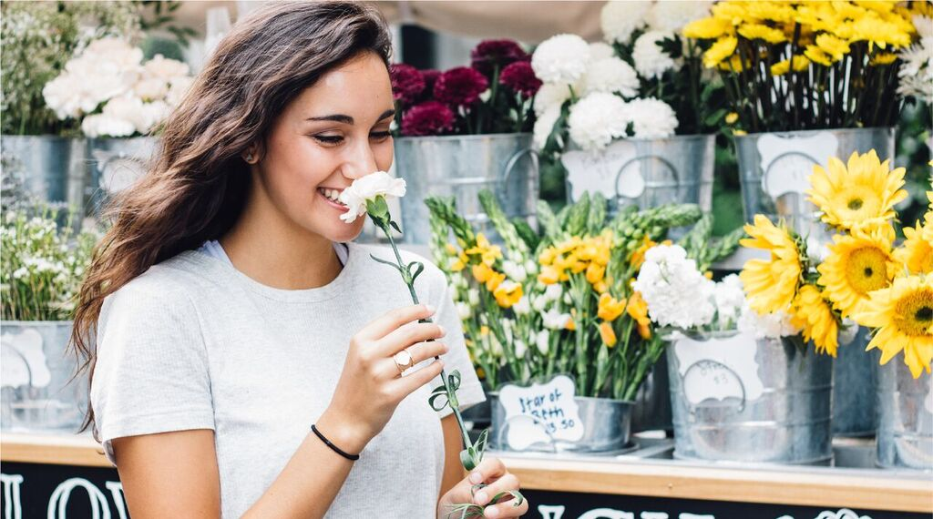 A girl smelling a flower with a smile