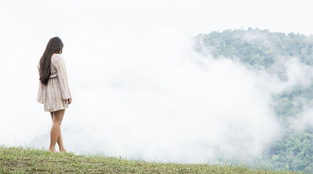 female sexual abuse survivor standing on a hill looking into a cloud