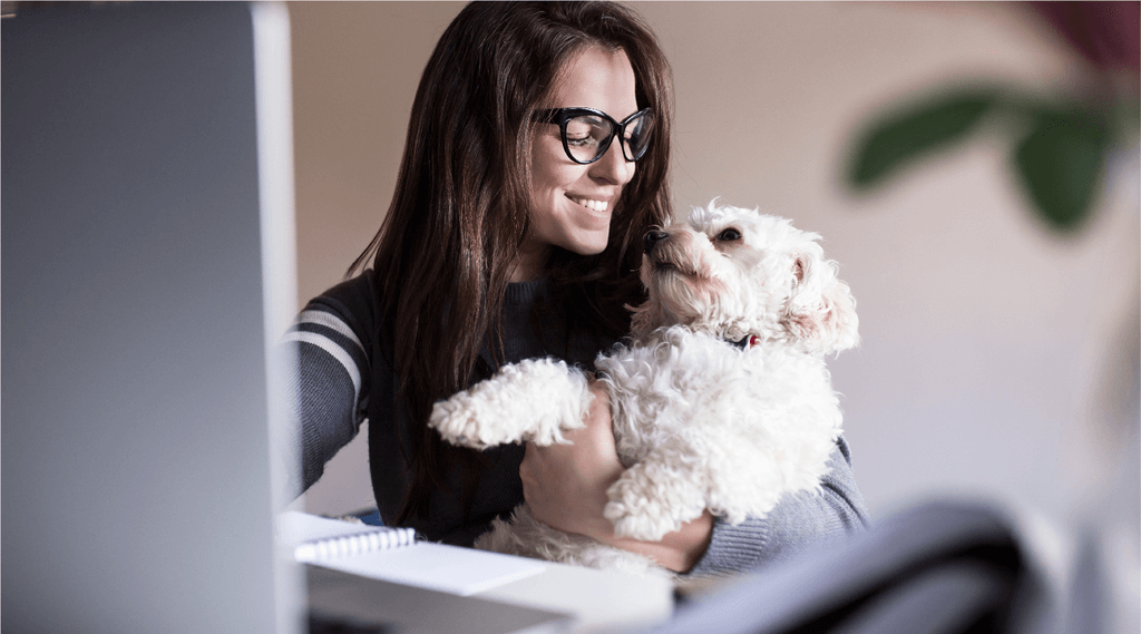 A woman with glasses holding her dog and looking at the dog